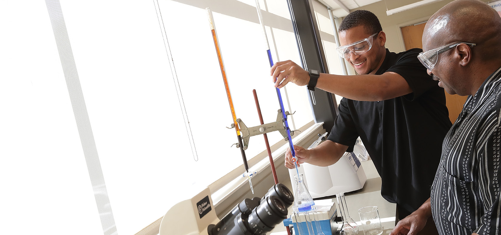 Dr. Mwangi helps USF student during Chemistry lab.
