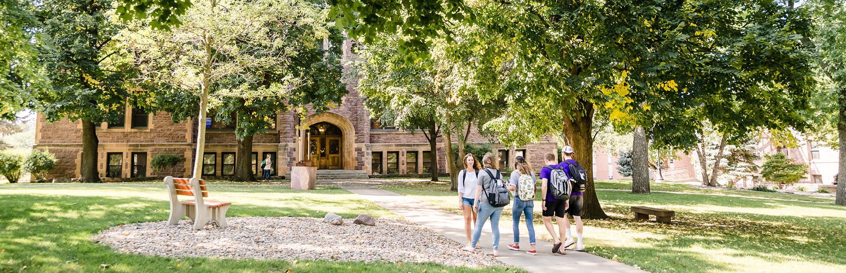 a sunny campus day outside Jorden hall on the quad with five students walking to class