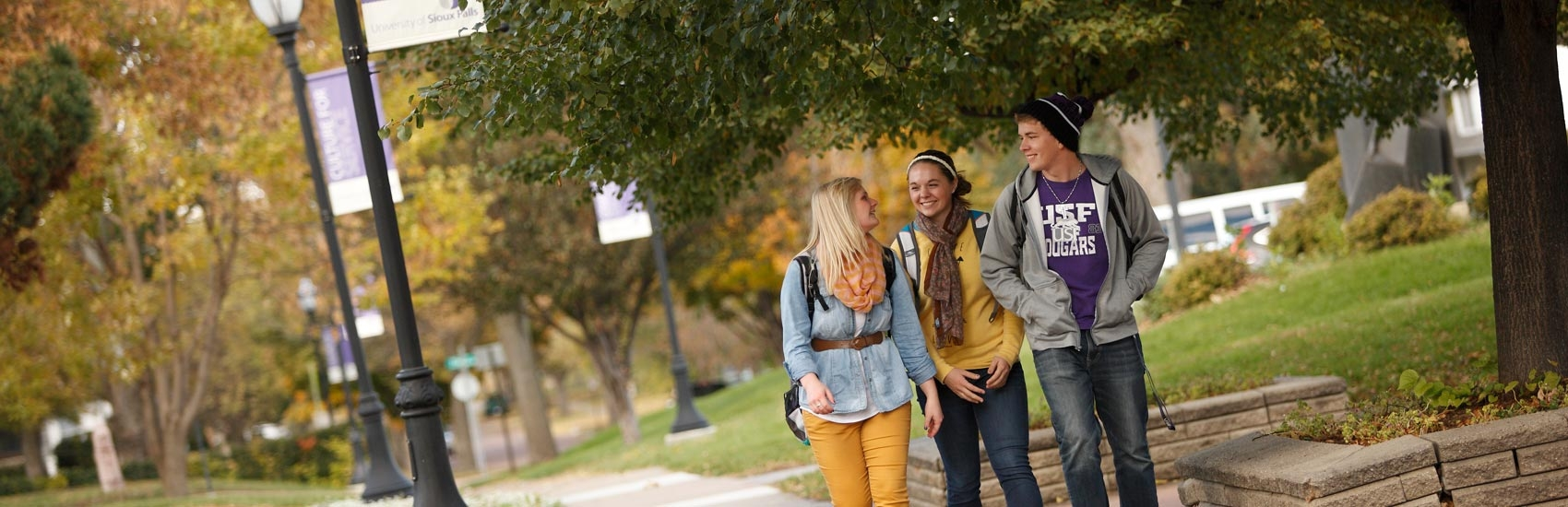 Students walking through campus in the fall.