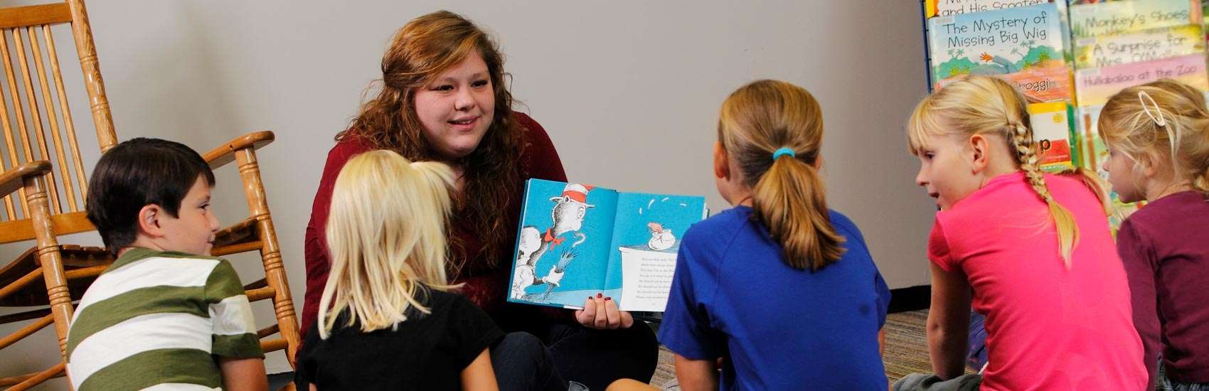 USF Elementary Education student reading a book to children.
