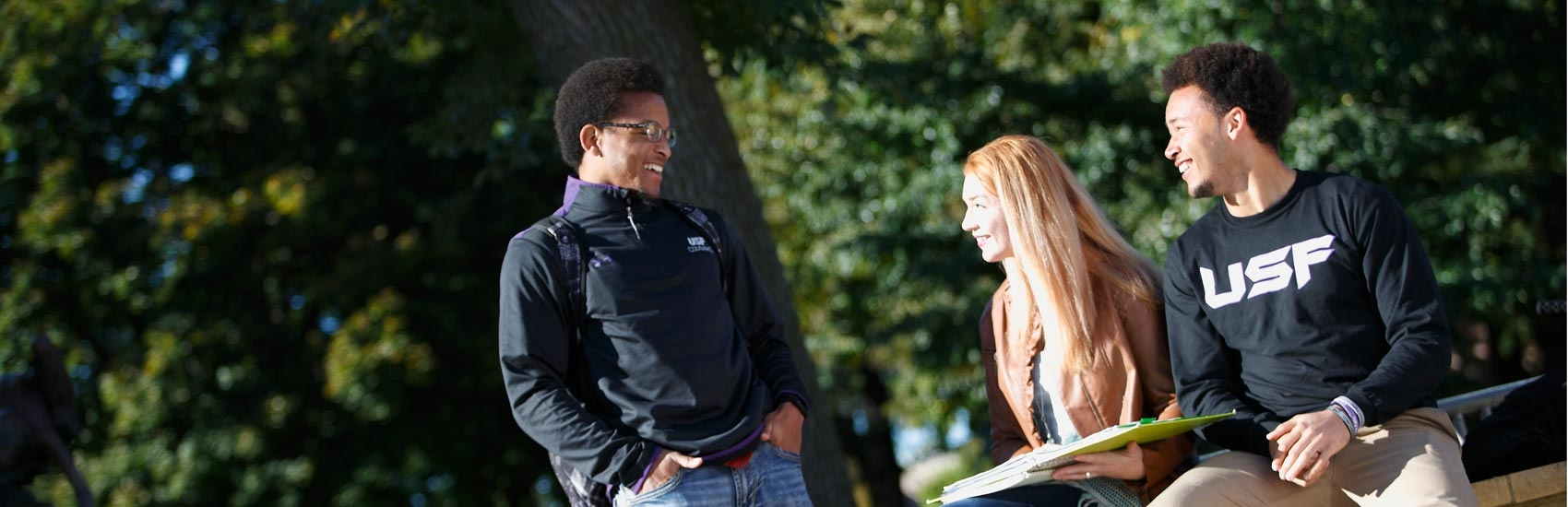 Students talking on USF's campus quad.
