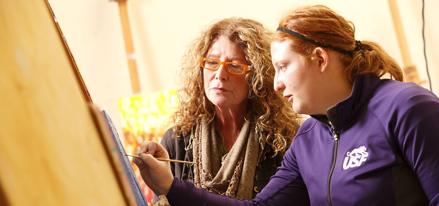 Professor Ceca Cooper helping a student with a painting.