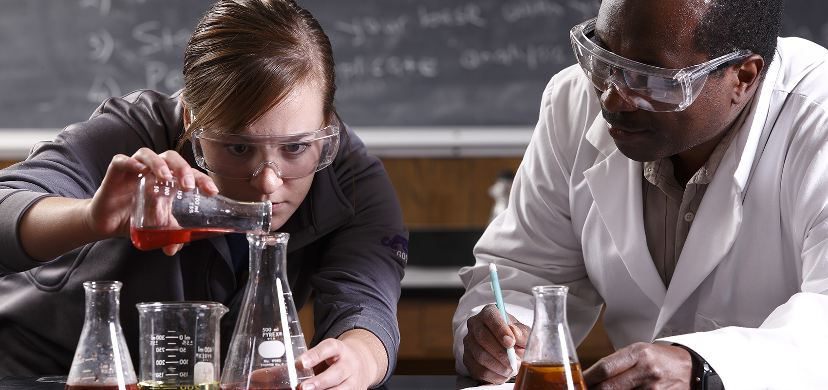 Professor George Mwangi working with a student during science lab.