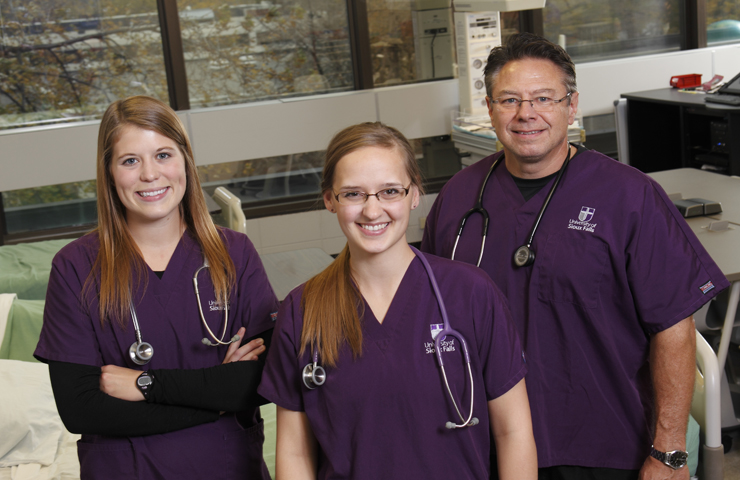 Three USF nursing students in simulation lab.