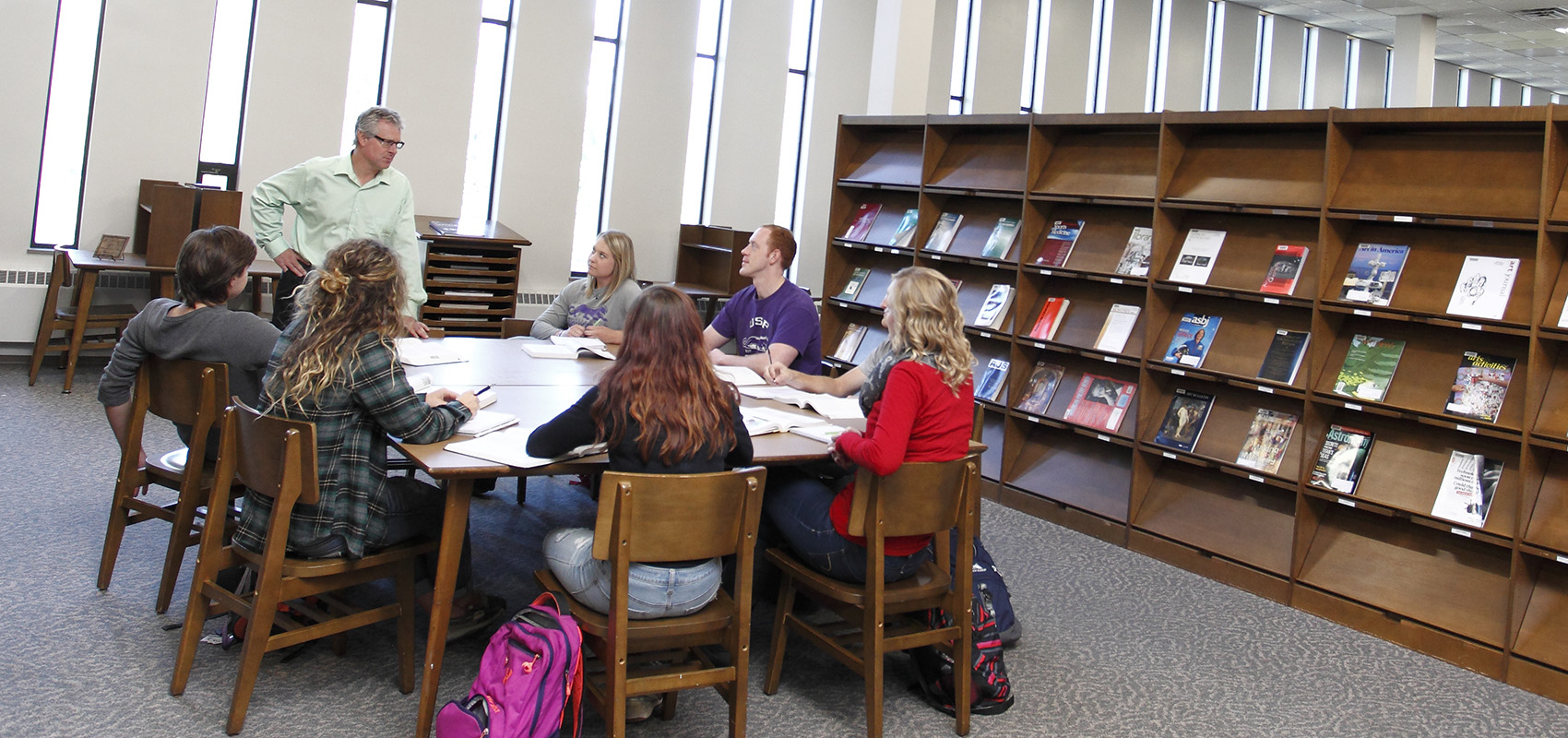 Professor Mike Grevlos teaching a psychology counseling class to USF students in the library.