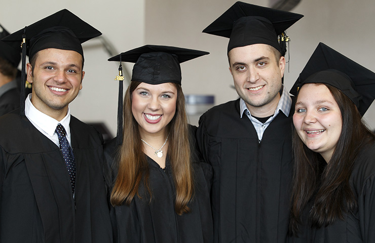 Four USF students at the Washington Pavilion on graduation day.